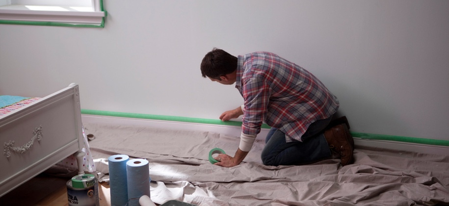 Une personne tapotant la plinthe avec du ruban Painters Mate Green.